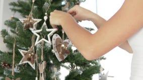 Kvinnan dekorerar julgranen stock video