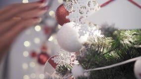 Kvinnan dekorerar julgranen med leksaker Julgran-, leksak- och handnärbildsikt arkivfilmer