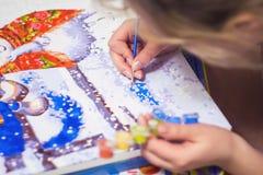 Kvinnan drar målarfärgen vid nummer Arkivfoton