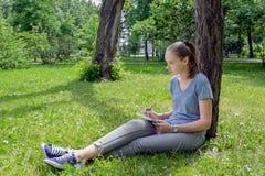 Kvinnan drar sammanträde på gräs Fotografering för Bildbyråer