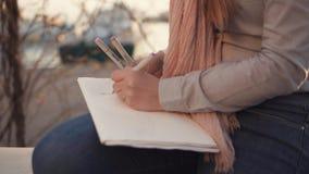 Kvinnan drar skissar av landskap i öppen luft i aftonen, närbild av händer stock video