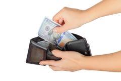 Kvinnan drar ut eller satte oss dollar från hennes handväska från hennes handväska Arkivbild