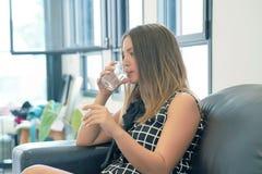 Kvinnan dricker en preventivpiller från smärtar royaltyfri fotografi