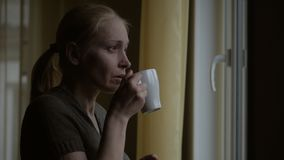 Kvinnan dricker en varm drink fr?n ett koppanseende p? f?nstret och blickar p? regnet till och med exponeringsglaset lager videofilmer