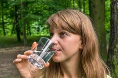 Kvinnan dricker exponeringsglas av vatten på den varma sommardagen Arkivfoton