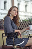 Kvinnan dricker kaffe i ett utomhus- kafé royaltyfri fotografi