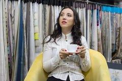 Kvinnan dricker kaffe i visningslokalen av tyger arkivfoton