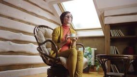 Kvinnan dricker kaffe på loft