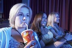 Kvinnan dricker läsken med vänner som håller ögonen på film i teater Fotografering för Bildbyråer