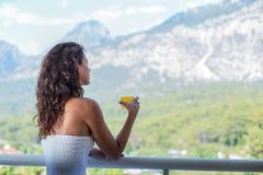 Kvinnan dricker orange fruktsaft på hotellbalkongen royaltyfria bilder