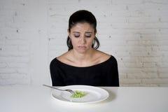 Kvinnan eller tonårigt med gaffeln som äter maträtten med löjlig liten grönsallat som hennes matsymbol av galet, bantar Royaltyfri Bild