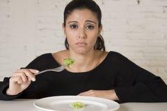 Kvinnan eller tonårigt med gaffeln som äter maträtten med löjlig liten grönsallat som hennes matsymbol av galet, bantar Royaltyfri Fotografi