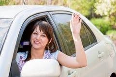 Kvinnan en chaufför efter rodern av bilen vågr en hand Royaltyfri Foto