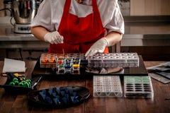 Kvinnan en konditor i röda enhetliga och vita handskar som gör godisen i sakkunnig, formar från mejerichoklad med ätligt arkivfoto
