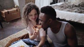 Kvinnan erbjuder att pizza ska man, men ska äta skivan av henne Blandras- par som har gyckel under målet med snabbmat Arkivfoto