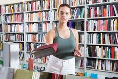 Kvinnan erbjuder en bok i en bokhandel fotografering för bildbyråer