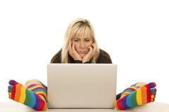 Kvinnan färgade sockor sitter vid datorhänder på framsida Arkivbilder