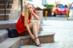 Kvinnan fäster hennes skor med höga häl Fotografering för Bildbyråer