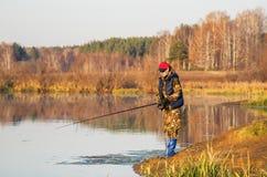 Kvinnan fångar en fisk på snurr Royaltyfri Foto