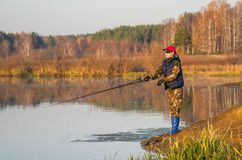 Kvinnan fångar en fisk på snurr Arkivbild