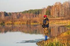 Kvinnan fångar en fisk på snurr Royaltyfri Fotografi