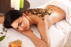 Kvinnan får en Marine Algae Wrap Treatment i den Spa salongen Arkivfoton