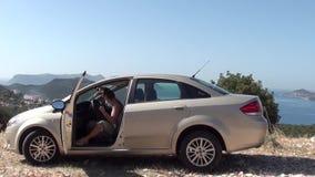 Kvinnan får i bilen och sätter på exponeringsglas arkivfilmer