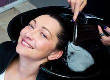 Kvinnan får tvagningen och att kamma för hår royaltyfri fotografi