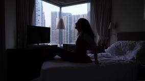 Kvinnan får upp från säng arkivfilmer