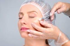 Kvinnan får utfyllnadsgodsinjektionen i kinder Anti--åldras behandling och framsidaelevatorn Kosmetisk behandling och plastikkiru Royaltyfri Bild