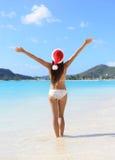 Kvinnan för bikinin för juljultomtenhatten på stranden semestrar Royaltyfria Bilder