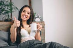 Kvinnan för den bra morgonen vaknade upp i säng dricka kvinna för underlagkaffe Royaltyfria Bilder