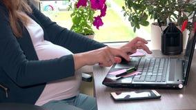 Kvinnan för den förväntansfulla modern räcker maskinskrivning på datortangentbordet och slaglängdbuken arkivfilmer