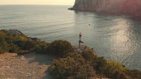 Kvinnan för den flyg- sikten gör yoga på solnedgången
