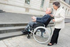 Kvinnan för den gamla kvinnan skjuter maken i rullstol Arkivbild