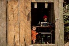 Kvinnan för den Hmong kullestammen använder symaskinen, medan hennes dotter poserar för foto Arkivbild