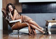 Kvinnan för den skönhetyong brunetten som hemma sitter nära spisen, övervintrar varm afton i inre som väntar för att fira royaltyfria bilder