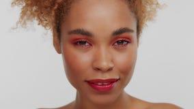Kvinnan för det blandade loppet med stort lockigt afro blont hår i studio bär ljus röd makeup arkivfilmer
