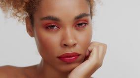 Kvinnan för det blandade loppet med stort lockigt afro blont hår i studio bär ljus röd makeup stock video