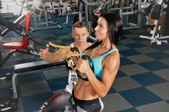 Kvinnan för kondition för manlig instruktörhjälp utför den unga övning med övning-maskinen Royaltyfri Fotografi