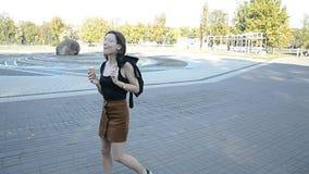 Kvinnan för lockigt hår som går i stad, parkerar och äter glass lager videofilmer