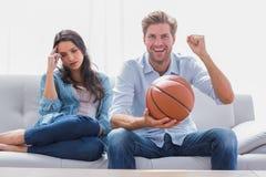 Kvinnan förargade av hennes hållande ögonen på basketmatch för partnern Arkivfoto