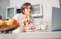 Kvinnan förbereder frukost- och klockabärbara datorn på kök Arkivbilder