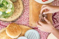 Kvinnan förbereder hamburgare som gör hamburgaren, ingredienser för att laga mat hamburgare på träskärbräda med rulle, grönsaker, arkivbild