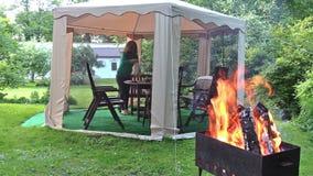 Kvinnan förbereder kvällsmåltabellen i utomhus- berså Vedträbrännskada stock video