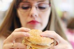 Kvinnan förbereder sig för att äta hamburgaren i kafét, fokus på hamburgaren royaltyfria bilder