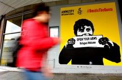 Kvinnan förbigår grafitti med de politiska sloganflyktingarna Welcom Arkivfoto