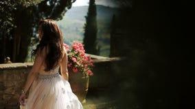 Kvinnan fördelar hennes eleganta klänning, medan hon virvlar på trädgård stock video