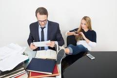 Kvinnan förhindrar en man för att arbeta Talande telefon Det Royaltyfri Foto