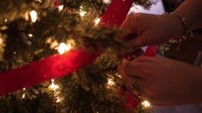 Kvinnan förlägger en fluga på en julgran runt om ferierna stock video
